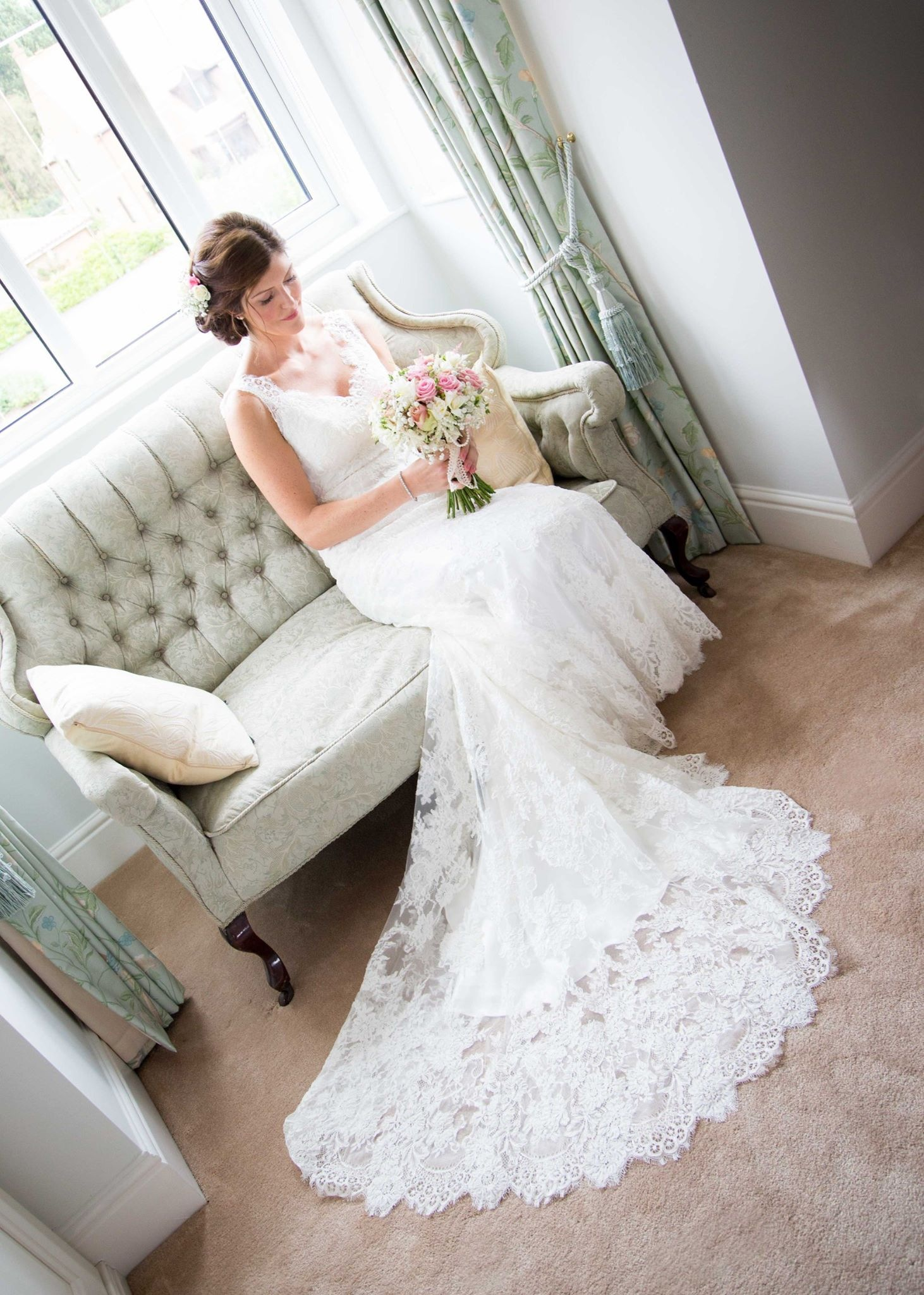 Bride with bouquet sat in window