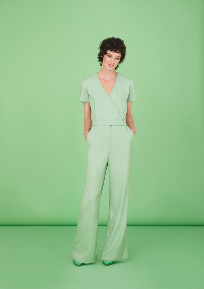 Woman with pixie hair wearing green silk jumpsuit